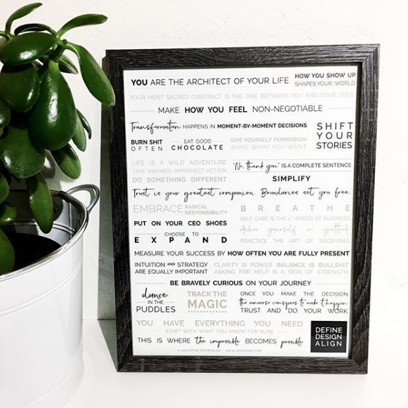 A framed manifesto poster next to a plant